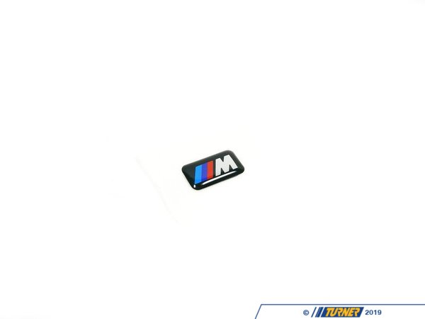 T#1129 - 36112228660 - M Sport Wheel Emblem (Genuine BMW) 18mm x 10mm - This self-adhesive backed emblem features the iconic BMW M logo and is used on all of the factory M Sport wheels, such as original M3 wheels, M5 wheels, M6 wheels, and many M wheels offered for non-M cars, such as the 740i Sport, and 330i sport & zhp packages (and others). Replace those missing or damaged ///M emblems with NEW factory fresh ones. It only takes a few seconds. Simply peel off the backing paper, and stick them on your wheels. These are the Genuine BMW emblems (not the shoddy / illegal knock-offs you'll find offered elsewhere for nearly the same price). These are sold individually, so be sure to order enough for all of your wheels (and your tool box!)  Installation Tip: We suggest cleaning the surface you are sticking this wheel emblem to before adhering it. This ensures the adhesive makes a tight bond, and your new M wheel emblems won't be going anywhere.  - Genuine BMW - BMW