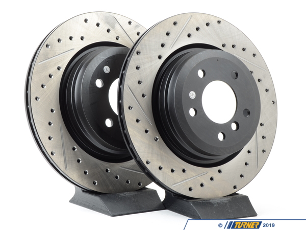 T#12056 - 34216764655CDS - Cross-Drilled & Slotted Brake Rotors - Rear - E90 330i/Xi, E9X 335i/Xi (pair) - Slotting a rotor helps to release gases that build up between the rotor surface and an out-gassing brake pad. Without an escape, this thin layer of gas will cause a delay until the pad cuts through gas layer. The slots in our rotors allow the gases to escape giving better braking performance. Cross-drilling a rotor is a way to improve initial pad bite. With the additional leading edges at each hole, the pad is able to grab the rotor just a little bit harder. By combining both Cross-drilling and slotting, these rotors combine the best of both worlds. Fewer holes mean longer pad life with little penalty in the way of initial pad bite. These rotors feature a unique black electro-coating that is designed to prevent corrosion. Each rotor is e-coated then double-ground and balanced to ensure an even surface with no vibration. The e-coating is the best anti-corrosion protection currently available in replacement rotors. Most aftermarket rotors are not coated, allowing surface rust to form right away, which is unattractive when brakes can be seen through your wheels. These rear brake discs / brake rotors fit:2006 E90 330i, 330Xi sedan2007-up E90, E92, E93 335i/335Xi sedan, coupe, and convertible - StopTech - BMW
