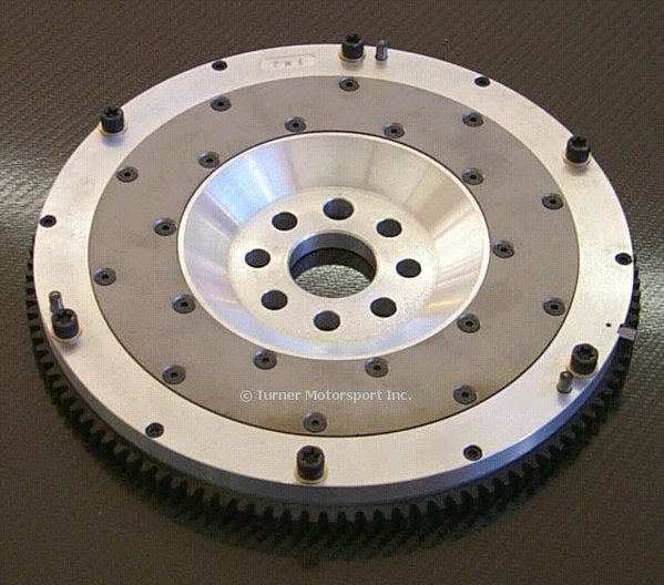 T#3767 - 520-020-228 - E30 325i, E34 525i, E36 325i JB Racing Lightweight Aluminum Flywheel (Replaces Dual-Mass Flywheel) - Aluminum flywheels are much lighter than the stock steel flywheel and that produces better throttle response and more available horsepower to the wheels for faster acceleration. The JB Racing aluminum flywheels are a direct replacement for the stock flywheel and work with stock clutch components for an easy upgrade with very little downside.Modern flywheels are built with additional components and features that are designed to dampen and minimize vibrations from the engine and transmission. As a result they have become bloated in weight and that means more energy is used up just making the flywheel spin. The weight difference between an aluminum and steel flywheel is huge - sometimes more than 50% less. Without the additional mass, more energy can be diverted to where it counts most - moving the car. The flywheel and clutch is one of the first areas that engine builders address when making the rotating assembly lighter for race engines. The dampening effect is just not needed on cars that are focused on performance.In addition to releasing more power to the wheels, the lighter flywheel allows the engine to spin more freely, which improves throttle response. Again, the difference is huge as you watch the revs build faster than before. With the engine spinning easier the power band comes up much sooner. The stock steel flywheel feels lazy in comparison. There is a driving adjustment required to get used to how much faster the engine revs but that's not really a downside.The JB lightweight flywheel is designed to be used with a factory organic clutch - the same clutch kit that you would get from any BMW dealer. This makes replacement clutch components easy to source and inexpensive when compared to specialized racing clutches. By using the factory BMW clutch, JB has also made the whole assembly easy to live with when used on the street. The clutch behaves the same as it originally did - just with better throttle response and more power! The JB flywheel can also be rebuilt with a new clutch contact surface - you don't have to buy a new flywheel.Aluminum flywheels are considered 'single-mass' flywheels because they do not have the same dampening designs as an original 'dual-mass' flywheel. With a single-mass design more noise and vibration may be noticeable. There are steps you can take to minimize the noise - heavier weight transmission oil and clutch discs with anti-rattle springs (sprung-hub clutch).On the E30 325i, this flywheel replaces the stock original dual-mass flywheel and should only be used with the corresponding 'dual-mass' clutch kit. According to BMW the dual mass flywheel was installed in all 325i from 12/86 on but we have seen some later cars with a single-mass flywheel. The age of the car almost guarantees one or more clutch replacements and possibly a change to the original flywheel as well. You may not know which flywheel is currently installed until the flywheel cover or the transmission is removed.Stock Flywheel Weight = 24.5lbsJB Flywheel Weight = 10.0lbsThis item fits the following BMWs:1986-1991  E30 BMW 325i 325ic 325is 325ix1992-1995  E36 BMW 325i 325is 325ic1989-1995  E34 BMW 525i - JB Racing - BMW