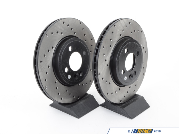 T#12153 - 34116774986CD - Cross-Drilled Brake Rotors - Front - MINI Cooper S R56 2007+ (pair) - Direct replacement Front cross-drilled brake discs for the MINI Cooper S R56. These rotors feature a unique black electro-coating that is designed to prevent corrosion. Each rotor is e-coated then double-ground and balanced to ensure an even surface with no vibration. The e-coating is the best anti-corrosion protection currently available in replacement rotors. Most aftermarket rotors are not coated, allowing surface rust to form right away, which is unattractive when brakes can be seen through your wheels.A cross-drilled rotor helps to release gases that build up between the rotor surface and an out-gassing brake pad. Without an escape, this thin layer of gas will cause a delay until the pad cuts through gas layer. The holes in our rotors allow the gases to escape giving better braking performance.This item fits the following MINIs:2007+  R56 MINI MINI Cooper S2007+  R55 MINI MINI Cooper S Clubman2007+  R57 MINI MINI Cooper S Convertible,  - StopTech - MINI